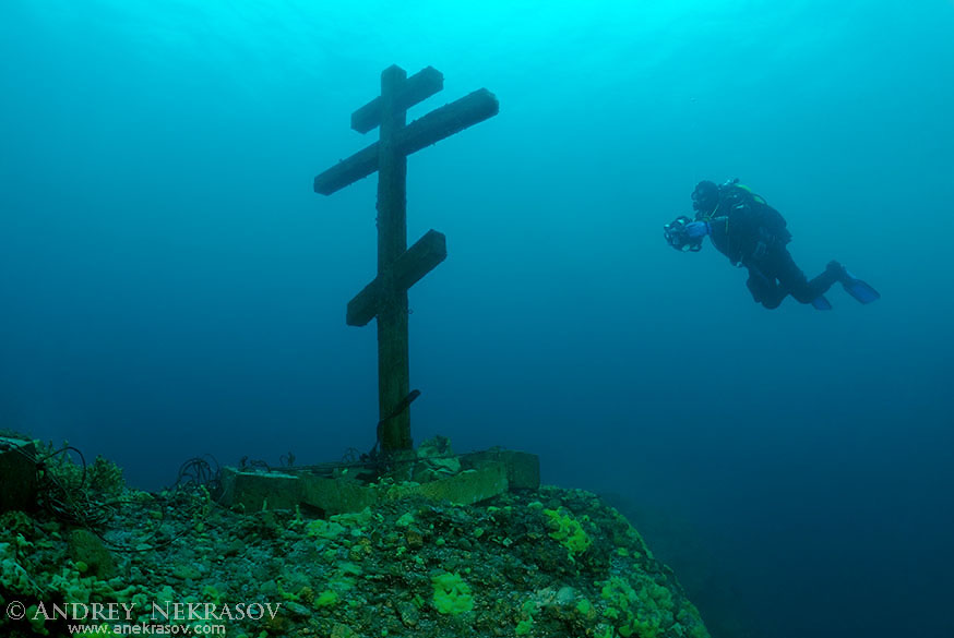 """The diver looks at a cross """"This cross is consecrated and established on Feast of the Ascension  09.06.2005"""". Lake Baikal, Siberia, the Russian Federation, Eurasia."""