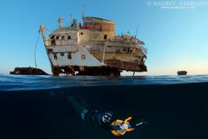 Freediver swims to underwater scooter near the wreck, Red Sea, Egypt