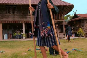 Children Tai Dam  learn to walk on bamboo stilts, Loei province, Thailand