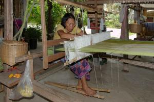 An elderly Tai Dam woman working on old wooden loom, Loei province, Thailand