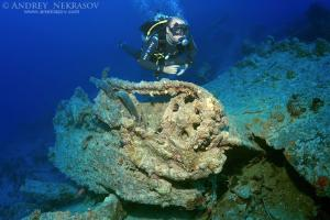 Diver looking at inverted tank on shipwreck SS Thistlegorm. Red sea, Egypt, Africa