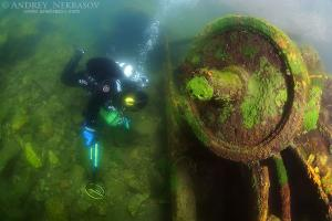 Diver with the metal detector searching for underwater treasure near to the wrack railway carriage, lake Baikal, Siberia, Russia, Eurasia