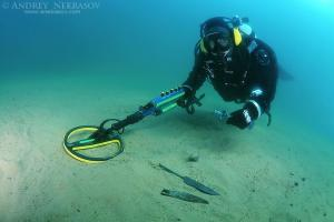 Diver with the metal detector shows found an ancient spearhead.  lake Baikal, Siberia, Russia, Eurasia