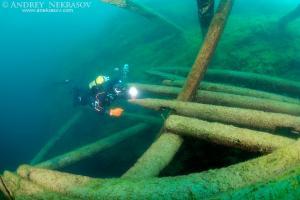 Diver surveys the destroyed wooden mooring, lake Baikal, Siberia, Russia, Eurasia