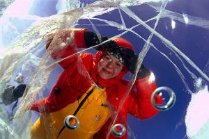 The woman looks through ice. lake Baikal, Siberia, Russia, island Olkhon.