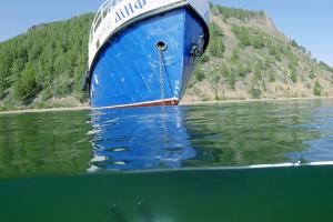 diver swims under the boat, lake Baikal, Siberia, Russia, Eurasia