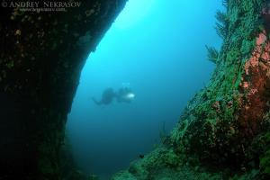 Diver looking into the cave, lake Baikal, Siberia, Russia, Eurasia