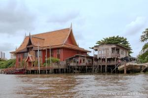 Old wooden house on stilts  in traditional Thai style on the Chao Phraya River, Bangkok, Thailand