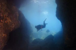Diver looking into the cave. Bohol Sea, Cebu, Philippines, Southeast Asia