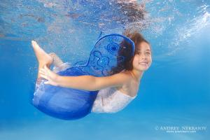 Girl presenting underwater fashion in pool